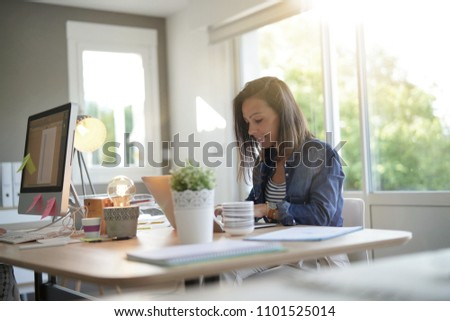 Cheerful girl working in co-working office #1101525014