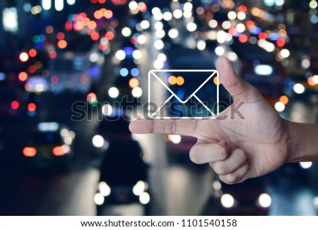 Mail icon on finger over blurred colourful night light city with cars, Contact us concept #1101540158