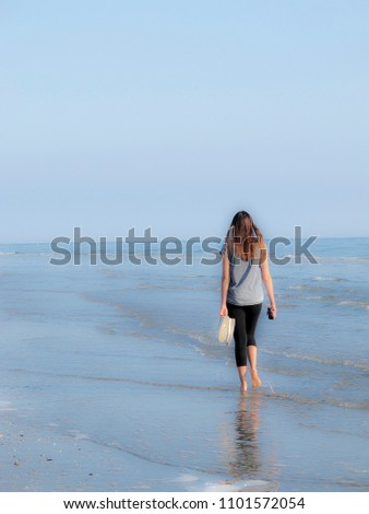 Beach of the Romagna coast (Italy): at sunrise a girl walks alone in the sea water, with shoes in hand #1101572054