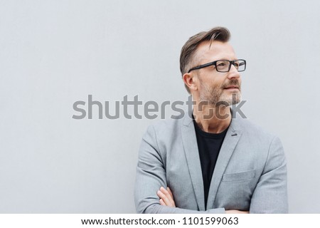 Portrait of mature man wearing grey jacket standing against white wall with copy space #1101599063