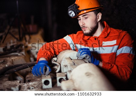 workers of the mining industry, to extract coal. repair of mine equipment. work in the mine. an engineer at the factory. repairs the mechanism. industrial enterprise. #1101632933