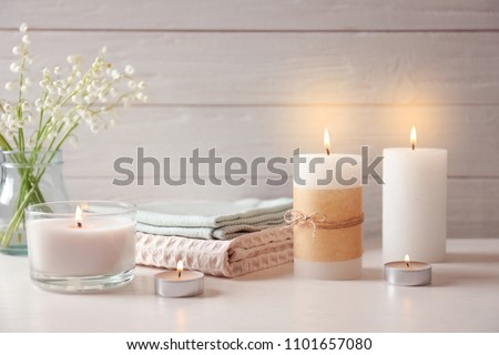 Beautiful composition with burning wax candles on table Royalty-Free Stock Photo #1101657080