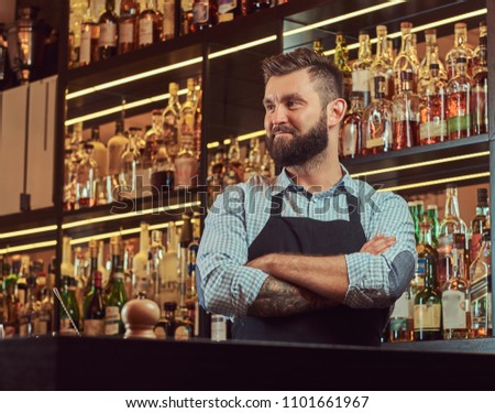 Stylish brutal bartender in a shirt and apron standing with crossed arms at bar counter background. #1101661967