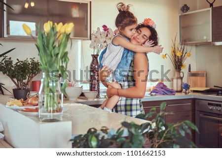 Sweet little girl kisses her mom while sitting in her arms in a kitchen.