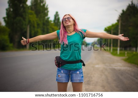 hitchhiking smiling girl with pink hair on road in travel time #1101716756