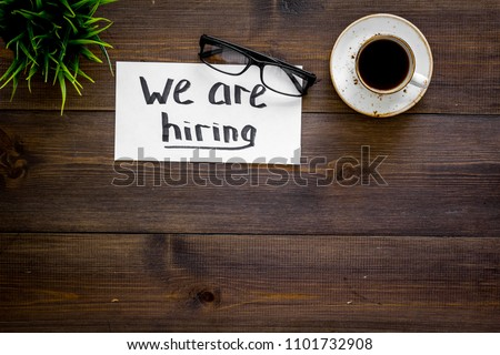 Search for worker, employee concept. We are hiring lettering on work desk on dark wooden background top view copy space Royalty-Free Stock Photo #1101732908