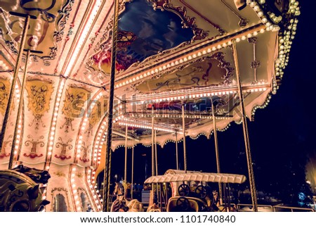 Children's Carousel at an amusement park in the evening and night illumination. amusement park at night. Outdoor vintage colorful carousel in the the city. Vintage photo processing Royalty-Free Stock Photo #1101740840