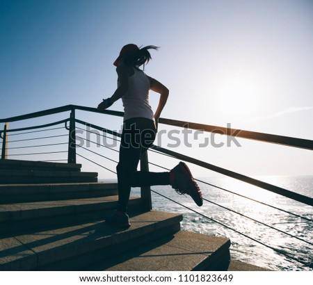 Sporty fitness female runner running up on seaside stairs #1101823649
