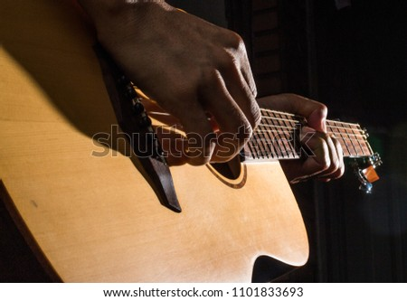 playing acoustic guitar on low-key lighting background #1101833693