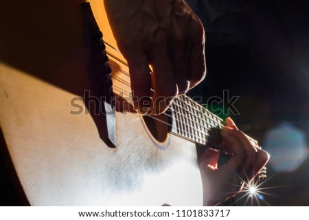playing acoustic guitar on low-key lighting background #1101833717