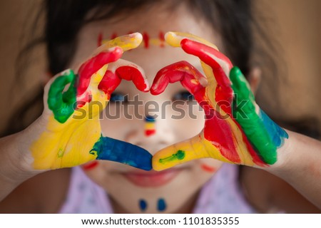 Child's hand with painted colorful watercolor make heart shape with love #1101835355