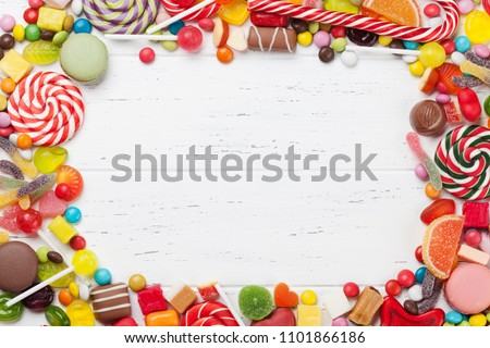Colorful sweets. Lollipops and candies. Top view with space for your greetings Royalty-Free Stock Photo #1101866186