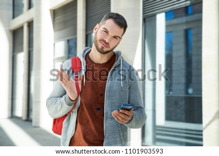Modern sports attractive man in a sports jacket and backpack holding a smartphone and smiling against the background of the modern city and the street. #1101903593