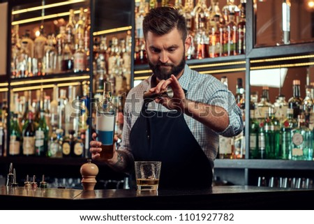 Stylish brutal barman in a shirt and apron makes a cocktail at bar counter background. #1101927782