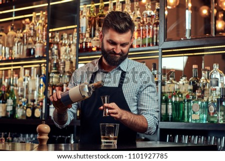 Stylish brutal barman in a shirt and apron makes a cocktail at bar counter background. #1101927785