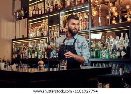 Stylish brutal barman in a shirt and apron makes a cocktail at bar counter background. #1101927794