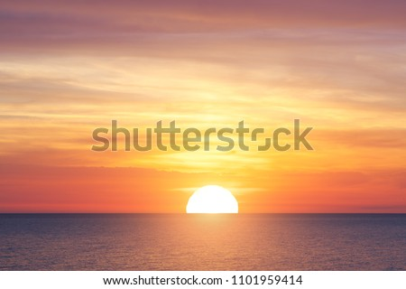 Bright sunset with large yellow sun under the sea surface #1101959414