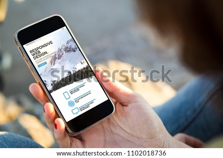close-up view of young woman checking responsive website on her mobile phone. All screen graphics are made up. #1102018736