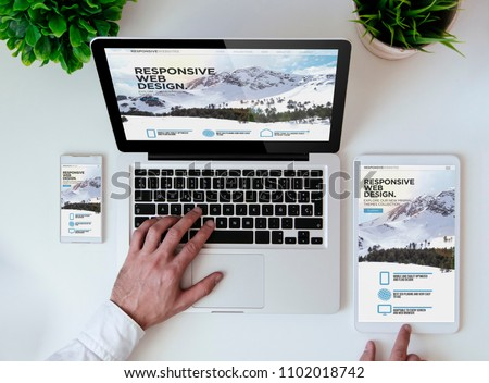 office tabletop with tablet, smartphone and laptop showing cool responsive design website #1102018742