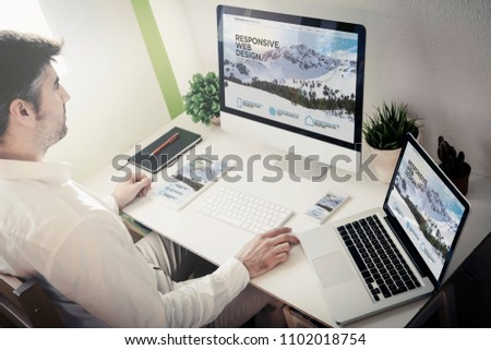 man working with devices with responsive website. All screen graphics are made up. #1102018754
