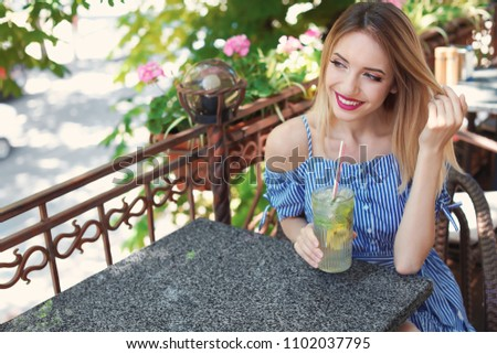 Young woman with glass of tasty lemonade at table in cafe, outdoors. Natural detox drink #1102037795