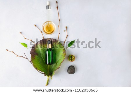 Organic Spa Cosmetic With Herbal Ingredients. Vegetable serum for skin. Serum with herbal extracts. Serum in a transparent glass bottle with a pipette and green twig on a white background #1102038665