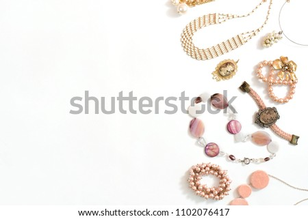 Set of women's jewelry in vintage style necklace cameo pearl bracelet chain earrings on white background. The view from the top lay flat. #1102076417