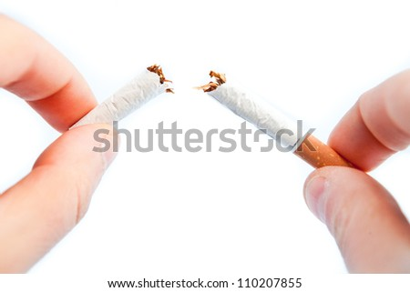 Fingers breaking a cigarette against a white background #110207855