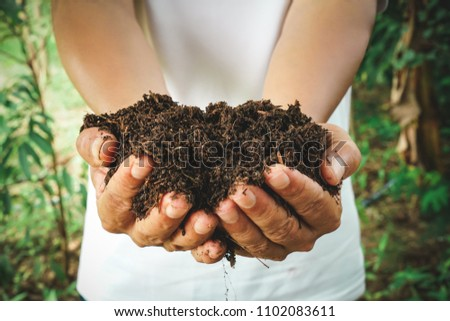 Farmer holding pile of arable soil, male agronomist examining quality of fertile agricultural land. The concept of fertility and caring for nature.  #1102083611