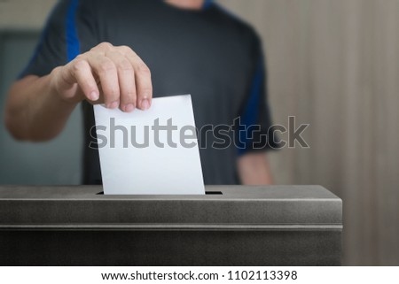 Election vote, hand holding ballot paper for election vote concept at place election background. #1102113398