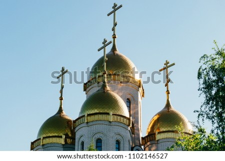 Beautiful church in the background of a clear sky. Sunny day. Golden domes and orthodox crosses. Traditional church in a green forest #1102146527