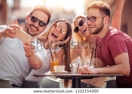 Four laughing friends enjoying coffee in a cafe.They are having a great time together. #1102154300