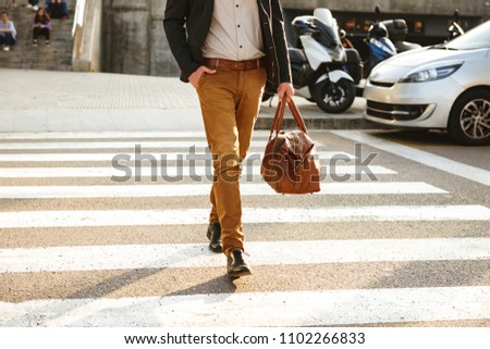 Cropped photo of stylish successful man in business wear walking through pedestrian crossing in downtown with leather male bag in hand #1102266833
