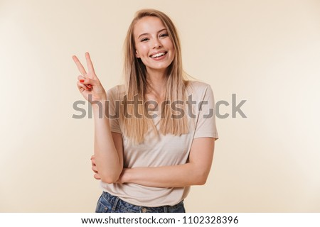 Image of cheerful caucasian woman wearing casual clothing smiling and showing peace sign with two fingers isolated over beige background in studio #1102328396