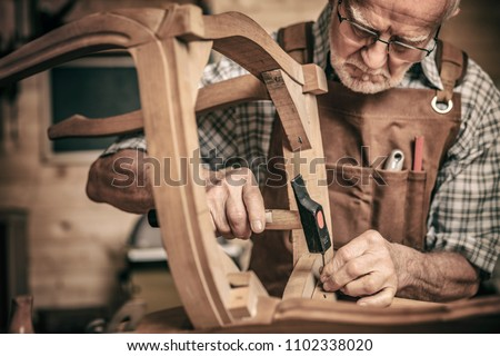 elderly carpenter builds a classic style chair #1102338020