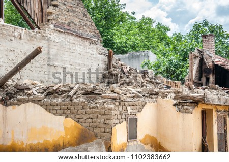 Aftermath damaged and collapsed roof on ruined house with wooden construction frame and brick wall #1102383662