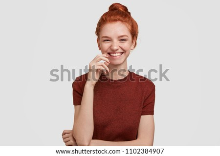 Pretty young delighted female has foxy hair combed in bun, smiles gladfully at camera, expreses happiness as finds out about her pregnancy, ready to start new life, tells good news to husband #1102384907