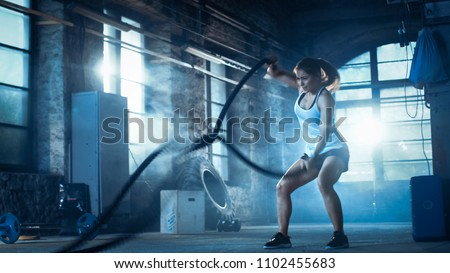 Athletic Female in a Gym Exercises with Battle Ropes During Her Cross Fitness Workout/ High-Intensity Interval Training. She's Muscular and Sweaty, Gym is in Deserted Factory. Cold Ambient. #1102455683