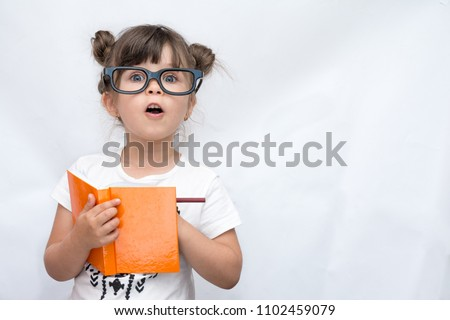 Surprised cute child in eyeglasses, writing in notebook using pencil, keeping mouth wide open. Four or five years old kid, isolated on white, space for advertising text #1102459079