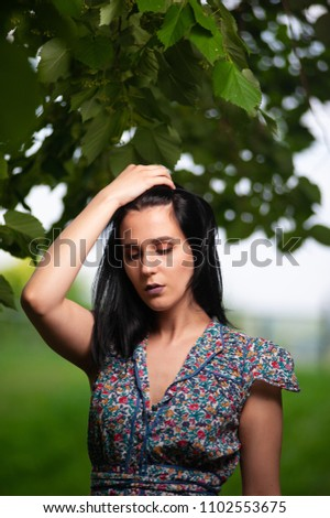 Young and beautiful girl portrait. She is holding her hand on her hair #1102553675