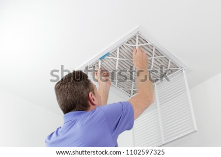 Person Removing Ceiling Air Filter. Caucasian male removing a square pleated dirty air filter with both hands from a ceiling duct. Guy taking out an unclean air filter from a home ceiling air vent #1102597325