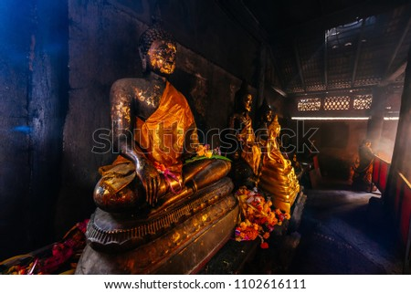 old bronze buddha statue with golden fabric in dark room, buddha statue in temple thailand people can go to see and worship #1102616111
