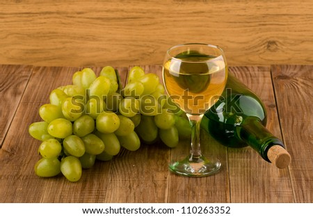 glasse of wine and bottle on a wooden table #110263352