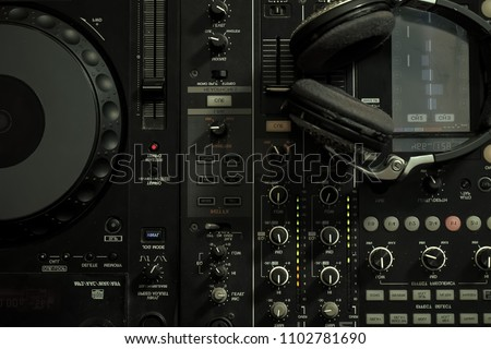 Upper view closeup of dj musical mixer professional console black color with many buttons and knobs and glamour headphones with pastes in night club or studio on digital background, horizontal picture
