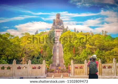 Young man traveler is visiting at The enormous Tian Tan Buddha at Po Lin Monastery in Hong Kong #1102809473