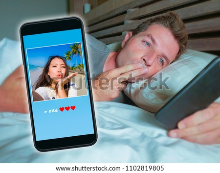 happy attractive man lying on bed sending good night kiss text with mobile phone having internet video call with Asian Chinese girlfriend in long distance relationship diversity couple concept  #1102819805