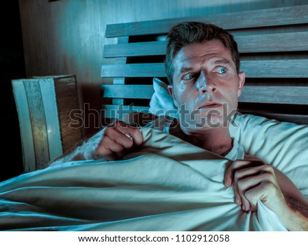 sleepless young man lying in bed stressed and scared suffering nightmare and horror bad dream grabbing duvet frightened and paranoid in sleeping disorder and resting problem lifestyle concept Royalty-Free Stock Photo #1102912058