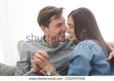 Happy young couple resting on sofa at home #1102929500