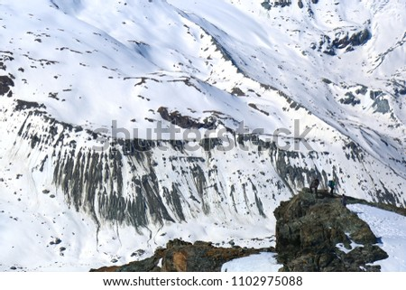 Tourists climb mountains  and stay on the edge of the rock on the background of peak mountains of Zermatt valley.  #1102975088
