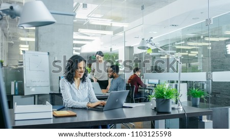 Busy International Office where Diverse Team of Young Businesswomen and Businessmen Work on Laptops, Have Meetings, Discussions and Draw Plans on a Whiteboard. #1103125598
